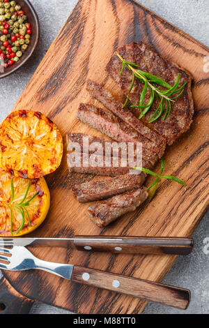 Sliced grilled beef barbecue steak with lemon, rosemary and spices on cutting board. Selective focus - Stock Photo
