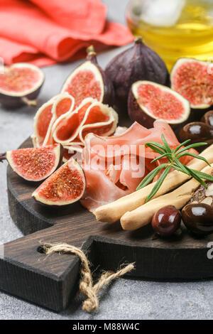 Appetizer of jamon, salami, bread sticks, Kalamata olives and figs on a cutting Board. Italian antipasti. Selective - Stock Photo