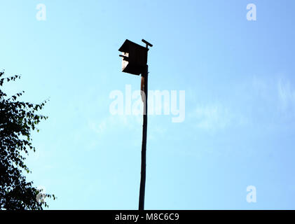 Wooden bird house on blue sky and lake background. Yellow birdhouse or nesting box on a leg. - Stock Photo