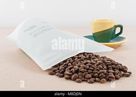 coffee envelope in open grains with colored cup - Stock Photo