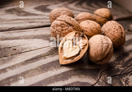 Walnuts on a grey textured wooden table. Assortment of nuts isolated on rustic old wooden background and splintered - Stock Photo
