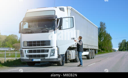 Truck Driver Gets out of His Parked White Cab-Over Truck. Day is Sunny, Driver is Professional. - Stock Photo