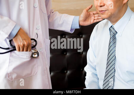 Handsome doctor is examining male patient's injured neck and giving a consultation to his patient - Stock Photo