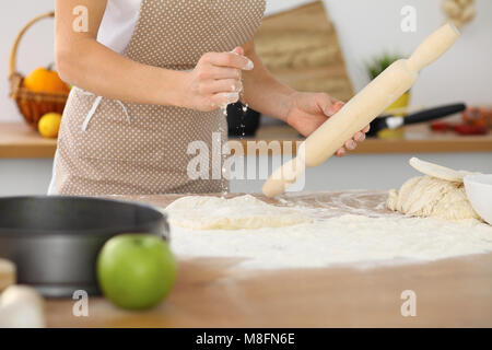 Female hands making dough for pizza or bread while using rolling pin. Baking concept - Stock Photo