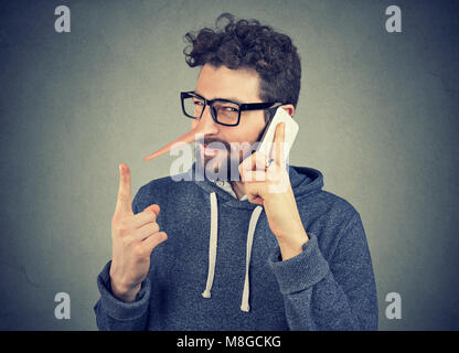young sly man with long nose talking on mobile phone isolated on gray wall background. Liar concept. Human emotion - Stock Photo