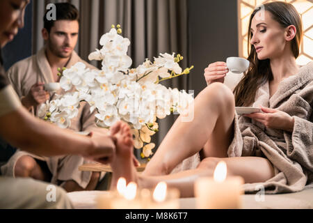 Beautiful woman drinking tea during therapeutic foot massage - Stock Photo