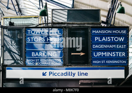 Old fashioned sign on the London Underground at Earl's Court Station pointing towards destinations within the London - Stock Photo