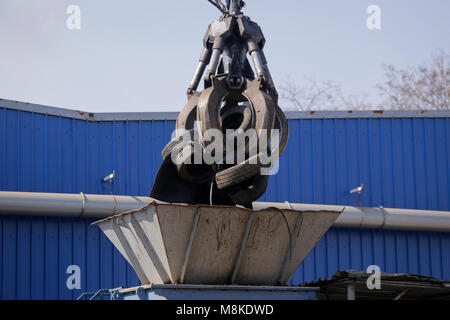 A worker uses a claw excavator to put used car tires in a shredder at a scrapheap junkyard - Stock Photo