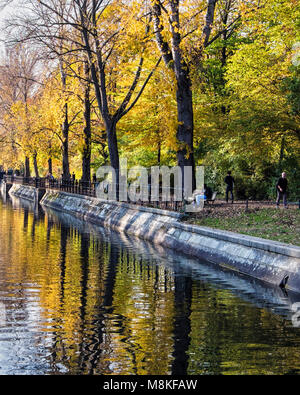 Colourful foliage of autumn trees next to the Landwehr canal & people walking on the tow path.. Kreuzberg, Berlin - Stock Photo