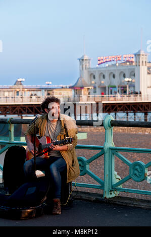 A busker entertains passersby with songs on Brighton's promenade near the famous Brighton Pier, one of the UK's - Stock Photo