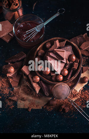 Wooden bowl with homemade chocolates and chocolate pieces, glazing with a whisk, scattered cocoa powder on a dark - Stock Photo