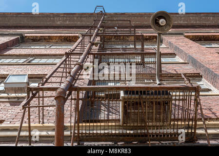 low perspective view of old steel fire escape outside brick building in inner city - Stock Photo