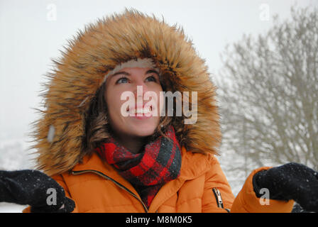 Portland, Dorset. 18th March 2018 - Rarely-seen snow on the Isle of Portland in Dorset ! A young woman with a furry - Stock Photo
