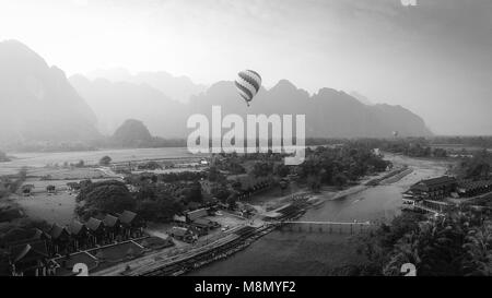 Aerial view by Drone : Hot air balloon over Nam Song river in Vang vieng, Laos on sunset. Black and white - Stock Photo