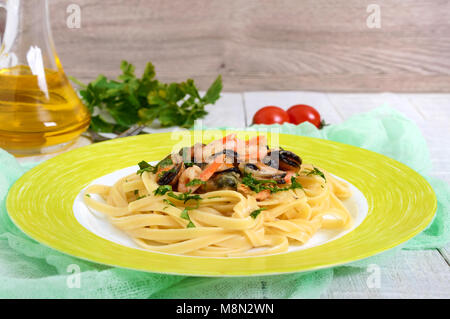 Pasta tagliatelle with seafood and cream sauce on a plate on a white wooden background. - Stock Photo