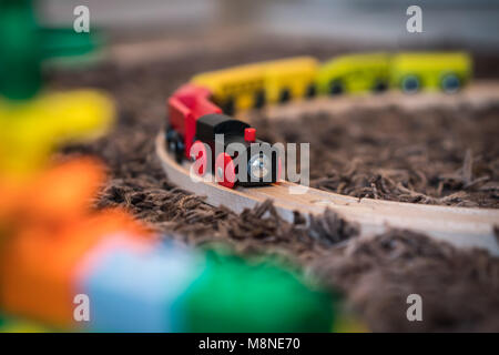 Colourful wooden toy train on the carpet in the living room in the house - Stock Photo