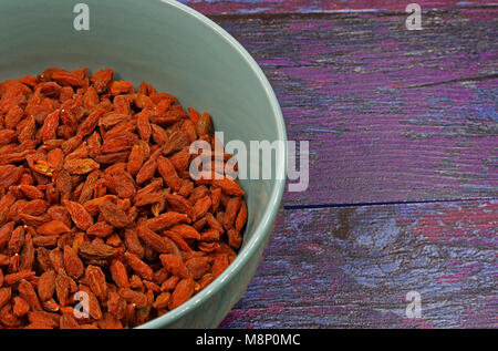 Ceramic bowl full of dry Goji berries on old wooden background in vintage style.Close , flat, horizontal view from - Stock Photo