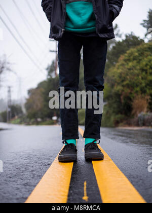 Low section of boy standing on wet road against sky during rainy season - Stock Photo