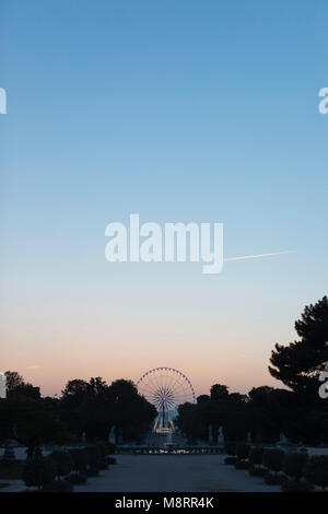 Ferris Wheel against sky at amusement park during sunset - Stock Photo