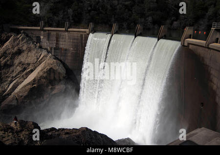 A lone woman climbs down the rocks to get a better view of the waterfall at North Fork Dam. - Stock Photo