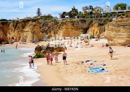 Tourists relaxing on Praia da Batata beach, Lagos, Algarve, Portugal, Europe. - Stock Photo