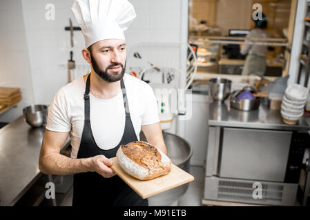 Baker with bread in the bakery - Stock Photo