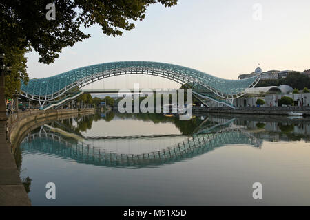 The Peace Bridge across the Mtkvari River and Presidential Palace on a hill in the background, Tbilisi, Georgia - Stock Photo