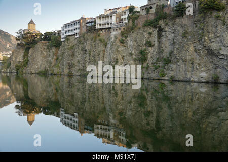 Metekhi Church and balconied buildings on a rocky cliff are reflected in the still waters of the Mtkvari (Kura) River, Tbilisi, Georgia - Stock Photo