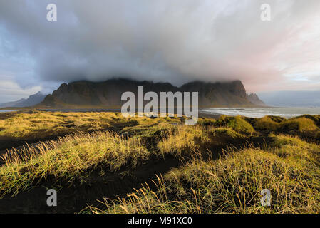 Magical Vestrahorn Mountains and Beach in Iceland at sunrise. Panoramic view of an Icelandic amazing landscape. - Stock Photo