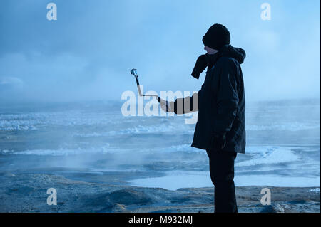 Namafjall geothermal fields, Iceland - March 2016: Man taking pictures with camera on selfie stick, surrounded by steaming, sulphurous mudpots - Stock Photo