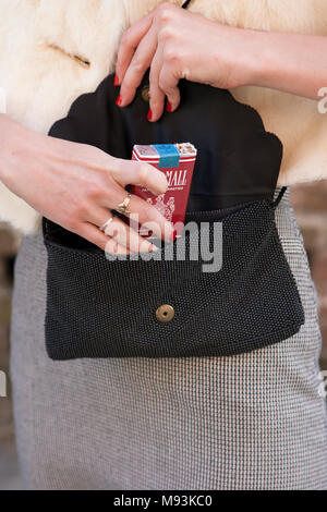 A woman reaching in her pocketbook for an open pack Pall Mall cigarettes. - Stock Photo