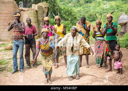 Somba village residents dance in front of their Tata Somba houses, northern Togo. - Stock Photo