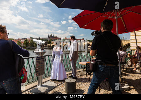 PRAGUE, CZECH REPUBLIC - JUNE 15, 2017: View of a wedding photo shooting session in front of the Charles Bridge and the Prague Castle on June 15, 2017 - Stock Photo