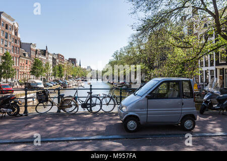 AMSTERDAM, NETHERLANDS - MAY 27, 2017: View of the water canal and parked small car und bicycles on Singel Street on May 27, 2017. Amsterdam is popula - Stock Photo