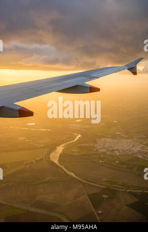 View from an airplane window during landing to the airplane wing with aerial view of the Andalusian landscape in Spain during evening sunset - Stock Photo