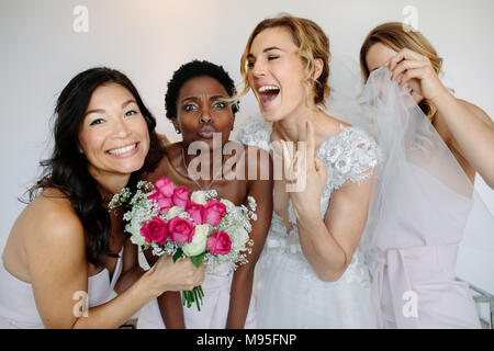 Portrait of cheerful bridesmaids with the bride in the room in the morning. Gorgeous bride in white dress having fun with beautiful bridesmaids in hot - Stock Photo