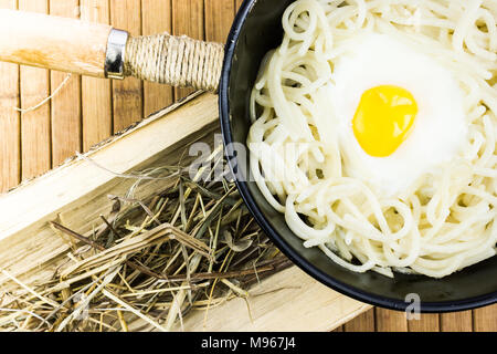 Fried egg and spaghetti in a black pan on a wooden table. Cooking at home, rustic food. - Stock Photo