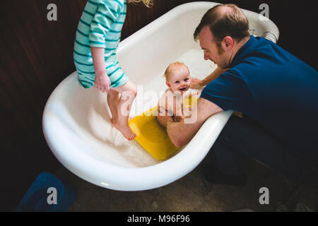 Father washing baby in tub with other girl - Stock Photo