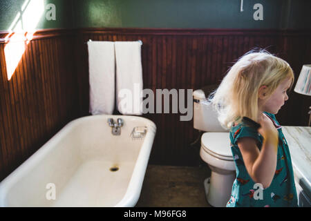 Girl combing her hair - Stock Photo