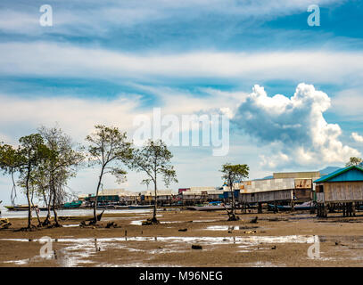 Village of Sea Gypsies during low tide. Asian traditional wooden houses on stilts. Floating houses village in Maumere, Flores Island, Indonesia - Stock Photo