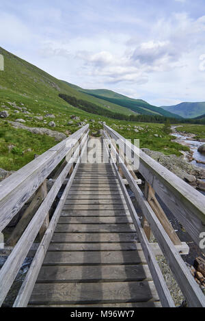 A small wooden Footbridge on the Path up Glen Doll in the Angus Glens and Cairngorm National park in the Highlands of Scotland. - Stock Photo