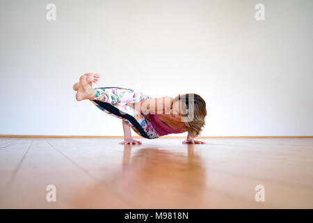 Mature woman practicing yoga on floor in empty room - Stock Photo