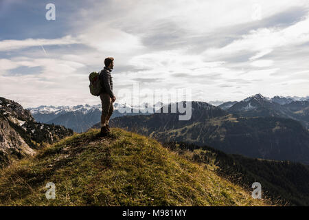 Austria, Tyrol, young man standing in mountainscape looking at view - Stock Photo