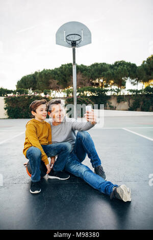 Father and son sitting on basketball outdoor court taking a selfie - Stock Photo