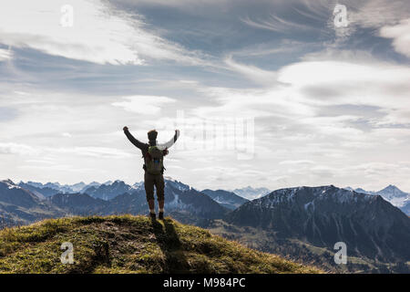 Austria, Tyrol, young man standing in mountainscape cheering - Stock Photo