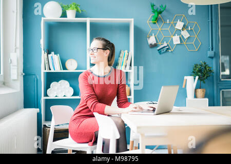 Smiling woman sitting at table with laptop looking out of window - Stock Photo