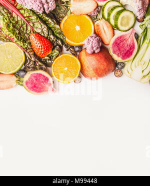 Variety of fresh colorful fruits and vegetables on white background, top view, border. Healthy food and clean eating concept - Stock Photo