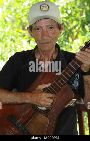 Portrait of cuban man in the 60s with a cap, holding his guitar in front of him. - Stock Photo