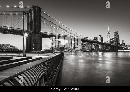Brooklyn Bridge Park boardwalk in evening with the skyscrapers of Lower Manhattan, East River, and the Brooklyn Bridge in Black & White. New York City - Stock Photo