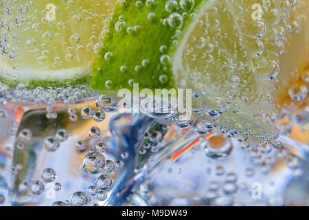 Homemade cocktail with citrus fruits in glass cup with transparent drink ices and bubbles. - Stock Photo